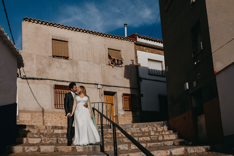 bride and groom kissing on the stairway