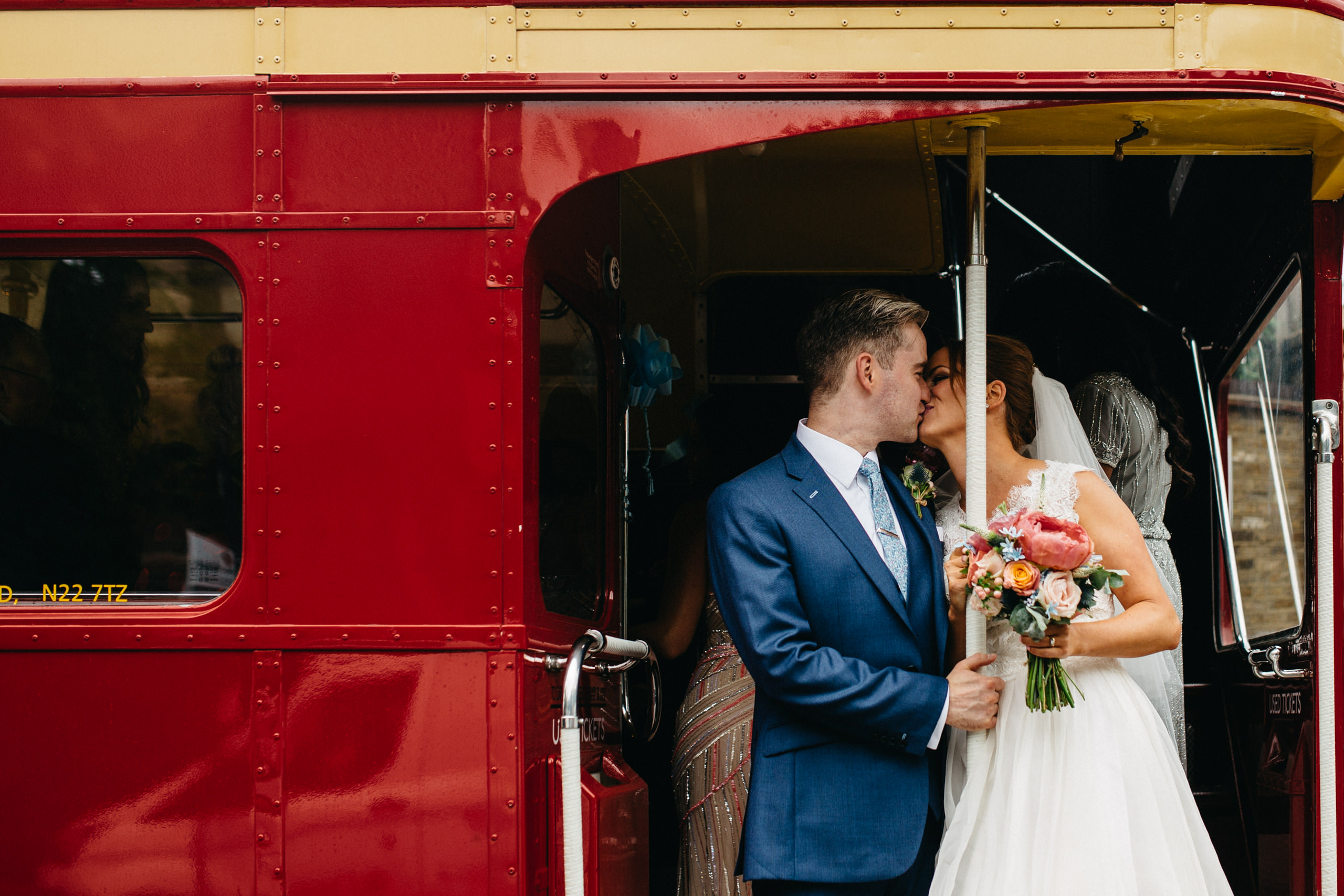 couple kissing in wedding bus in london