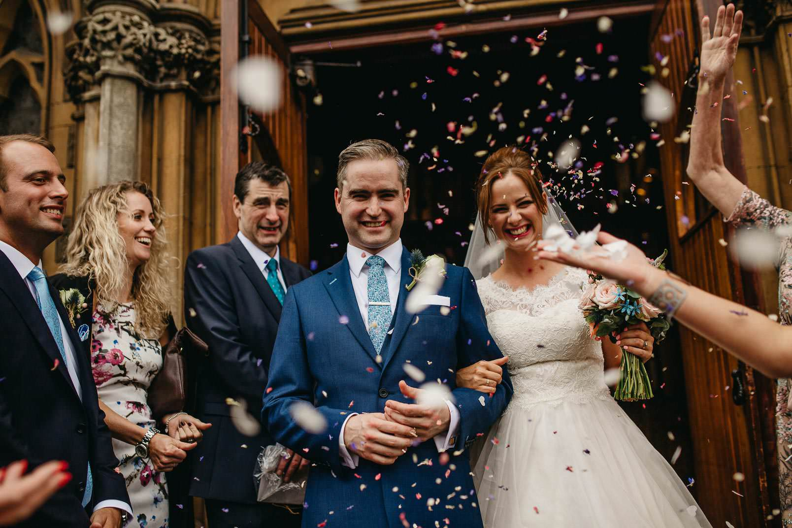 bride and groom walk when guests throw confetti